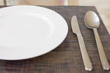 Close Up And Selective Focus Shot Of Tableware (white Plate, Fork, Spoon And Knife) On Table In Restaurant Which Is Well Prepared And Decorated For Lunch And Dinner Meal Or Food.