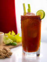 Clamato Drink With Spicy Chily On Top A Slice Of Lemon And Pieces Of Celerywith Peanuts On The Side And A Big Window In Th Backgroung, High Key Light