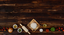 Tray Of Homemade Seafood Pizza Surrounded By Ingredients Located In Row Below The Wooden Background And Decorated With Dried Plants, Cold Beverage And Fried Potatoes With Copy Space.