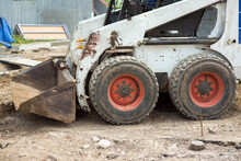 Mini Excavator At A Construction Site Loads The Ground With A Front Bucket, Close-up