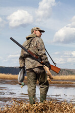 Hunter With A Duck Decoys In Both Hands Stands On The Shore