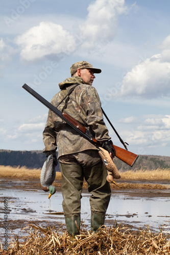 Canvastavla hunter with a duck decoys in both hands stands on the shore