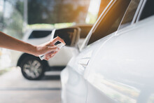 Woman Hands Spraying Alcohol On Car Door Handle,Preventive Measures Against Coronavirus,Covid-19 Pandemic