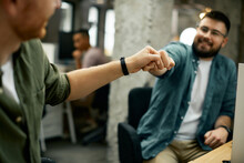Close-up Of Business Colleagues Fist Bumping In The Office.