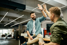 Happy Creative Business Colleagues Giving High-five To Each Other While Working In The Office.