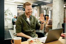 Happy Entrepreneur Waving During Video Call Over Laptop At Corporate Office.