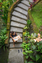 Woman Carrying Breakfast Tray Down Curved Stair Case Through Jungle Forest To A Bungalow In Bali.