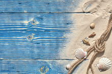Seashells And A Rope With Sand On A Blue Wooden Background