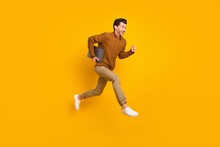 Full Size Profile Photo Of Impressed Nice Brunet Man Hold Laptop Run Wear Sweater Isolated On Yellow Background