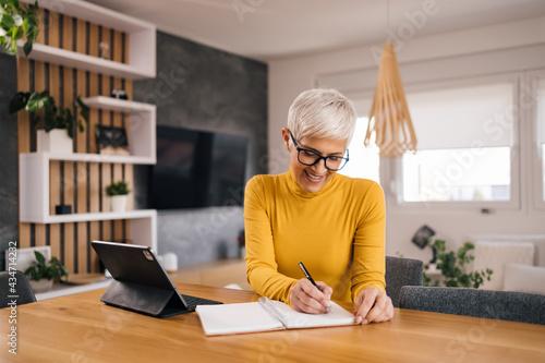 Happy senior woman writing down ideas, portrait.
