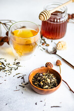 Cup Of Herbal Tea With Tea Leaves And A Pot Of Honey