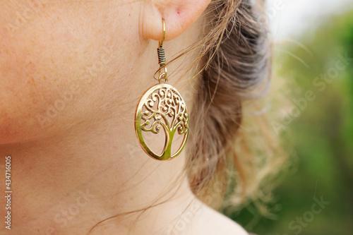 Fotografering Outdoor detail of female ear wearing metal round shape earring