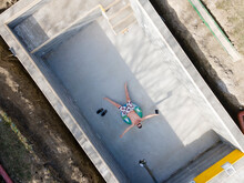 Man In Swimming Trunks Lies In Not Yet Finished Pool On A Floating Tire And Takes Selfie With Drone