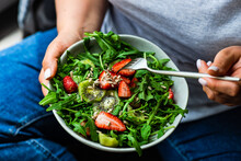 Close-up Of A Woman Eating A Bowl Of Rocket, Strawberry And Kiwi Fruit Salad With Sunflower Seeds And Chia Seeds