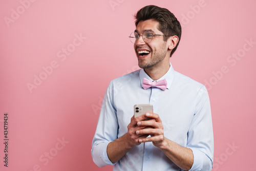 Obraz na plátně Young white man wearing bow tie laughing and using cellphone