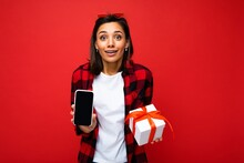 Photo Of Beautiful Positive Surprised Young Brunette Woman Isolated Over Red Background Wall Wearing White Casual T-shirt And Red And Black Shirt Holding White Gift Box With Red Ribbon And Mobile