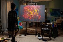 A Young Painter Stands In Her Studio Facing A Painting And Evaluates Her Project, A Work That Is An Abstraction. The Artist Holds A Paintbrush Soiled With Paint In Her Hand