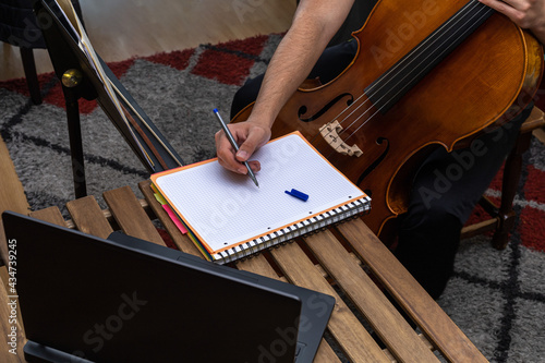 Wallpaper Mural young man taking online cello lessons with his laptop on a wooden table and writ