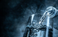 Pouring Water From Bottle Into Glass On Black Background