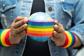 Asian lady holding rainbow color flag with globe, symbol of LGBT pride month celebrate annual in June social of gay, lesbian, bisexual, transgender, human rights.