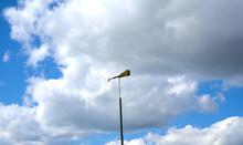 A Sign In The Form Of An Arrow Showing The Direction Of The Wind Against A Background Of Blue Sky And White Clouds. Bright Sunny Day