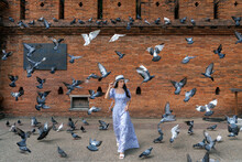 Full Length Of Woman Standing With Pigeons