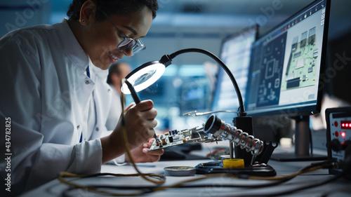Fotografia, Obraz Modern Electronics Facility: Beautiful Black Female Scientist, Engineer Does Printed Curcuit Motherboard Soldering