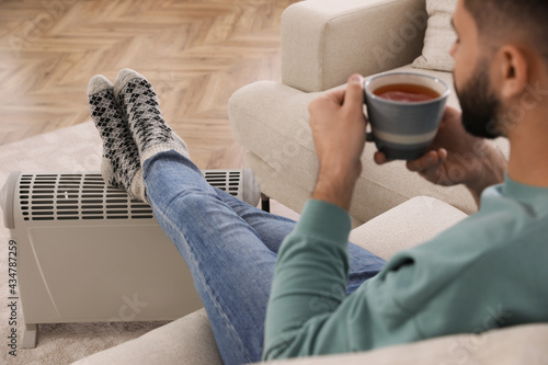 Fotografiet Young man with hot drink warming up near electric heater at home, focus on feet