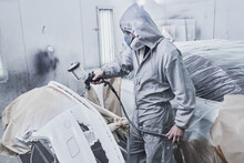 Car Painting And Automobile Repair Service. Auto Mechanic In White Overalls Paints Car With Airbrush Pulverizer In Paint Chamber.