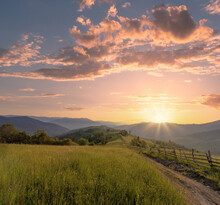 Beautiful Summer Evening Scenery With A Rural Road And Wooden Fence Along With It At Green Carpathian Mountains. Sun On A Beautiful Sunset Sky Is Shining Over Green Hills.