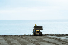 Preparing The Beach In The Early Morning With A Tractor In Russia. The Bulldozer Is Retracted On The Shoreline.