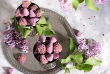 Belgian Sweets Cuberdon And Pralines In Silver Glasses, Spring Still Life With Lilac Flowers, Flat Lay