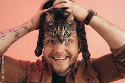 Fotografija Man holding his striped cat at his head and laughing while posing at the studio