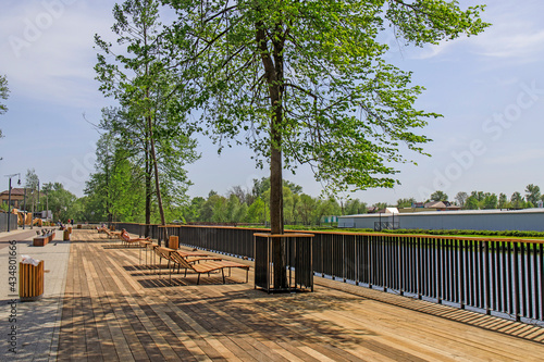 Fotografija A modern embankment equipped with sun loungers in the city on the banks of the Guslitsa River