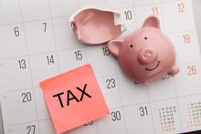 Broken Piggy Bank On A White Calendar Background, Tax Time Concept