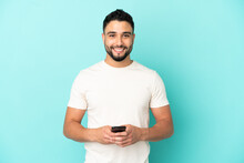 Young Arab Man Isolated On Blue Background Sending A Message With The Mobile