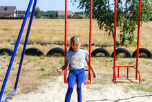 Defocus Little Girl Swinging On Swing On Playground With. Countryside Area. Bright Blue And Red Swing. Kids Summer Game. Girl Have Fun On Summer Holiday. Out Of Focus