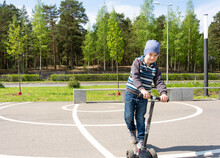 Boy With A Scooter Having Fun In The Park In The Spring
