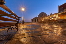 Old Venetian Harbor Ghania Creta Greece Towards To The Lighthouse In Dawn Ligth With Reflections In Puddles , A Bench Old Street Lights And Restaurants And The Mosque K K Hasan In The Foreground