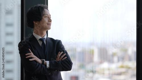 Fotografiet ビルの景色を眺めるビジネスマン