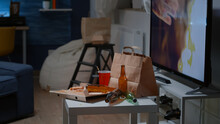 Close Up Of Table With Food And Booze Leftover On Misery Table In Empty Unorganized Dirty Living Room Of Depresive Alone Person. Untidy House Apartment Of Woman With Sever Depresion