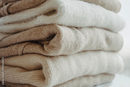 cozy milky beige and white natural wool sweaters, folded on a white background close-up Fototapeta