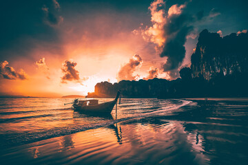 Amazing sunset with longtail boats silhouette at Railay beach, Thailand.