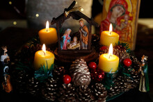 Christmas Crib And Natural Advent Wreath Or Crown  With Four Burning Yellow  Candles.  Christmas Composition.  France.