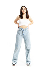 Beautiful Summer Girl In Casual Clothes Posing With Hands On Hips With Cocky Attitude. Full Body Length Isolated On White Background