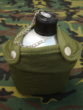 Closeup Of Aluminum Water Canteen On Camouflage Surface