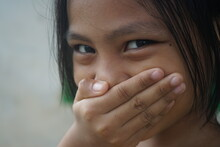 The Asian Girl Is Smiling While Covering Her Mouth
