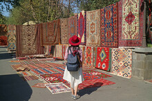 Female Traveler Impressed By The Stunning Carpets At Vernissage Market In Downtown Yerevan, Armenia