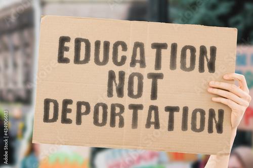 Fototapeta The phrase  Education not deportation  on a banner in men's hand