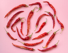 Flat Lay Dried Red Chili Peppers Pattern On A Pink Color Background.